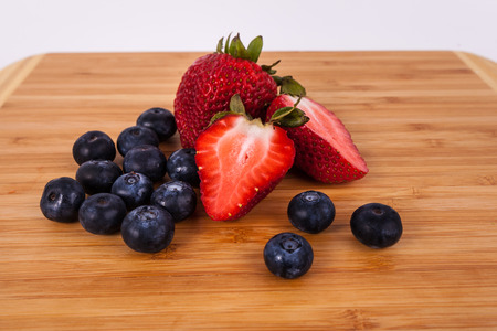 Red hole halved organic strawberries blueberries Stock Photo