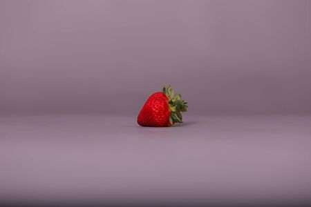 One isolated red ripe strawberry on a solid gray background captured in studio