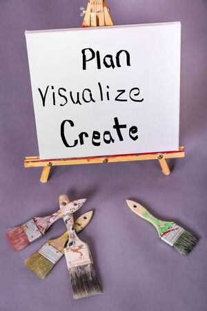 Painted words Plan Visualize Create painted on white canvas with black paint scattered paintbrushes