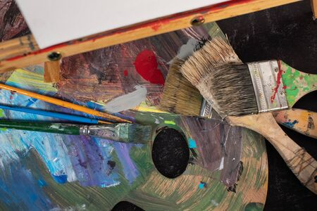 Art school materials wooden palette paintbrushes canvas and easel Фото со стока