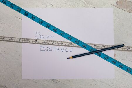Social distancing hand written on white paper with blue and white sewing tape measurers