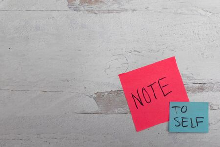 Pink and blue posted noted message of reminder note to self handwritten on white wooden background