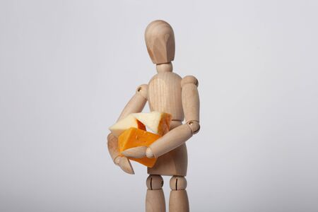 Close up of wooden jointed doll holding close assorted blocks of cheese