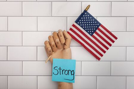 Fake wooden jointed hand holding an American flag with blue posted note with the word strong on it