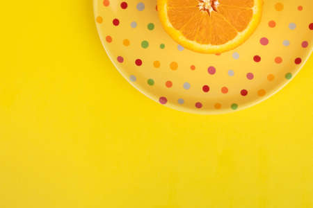 Bright yellow background dead space with poke a dot plate half an orange