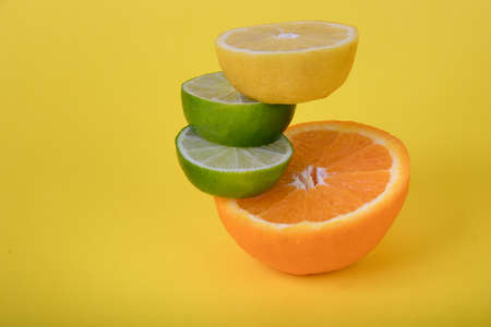 Fresh sliced orange lemon and limes uniquely stacked on a bright yellow background