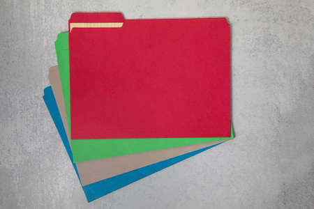 Assorted colors of file folders fanned out office materials and supplies flat lay background
