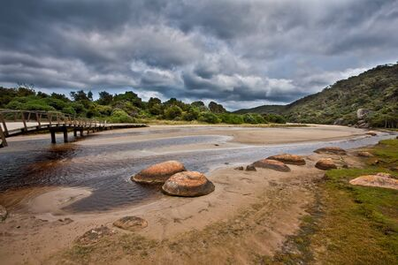 wilsons promontory: Wooden footbridge across Tidal River on stormy weather. Wilsons Promontory, Victoria, Australia