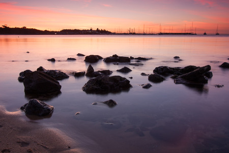 rock formation: Sunset over boats with rocks in foreground.