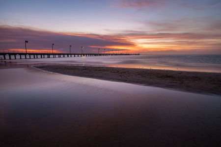 Smooth water surface and pier in orange sunset  colors.