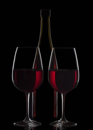 Red wine bottle and two wine glasses on black background Stock Photo