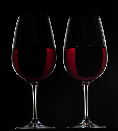 Two red wine glasses with wine on black background Stock Photo