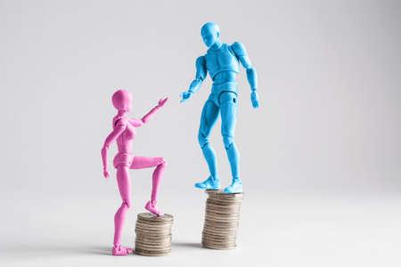 salarios: Concepto de desigualdad de ingresos mostrado con figurillas masculinas y femeninas realistas y pilas de monedas