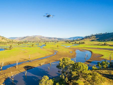 明るく晴れた日にオーストラリアの田舎上を高く飛ぶ無人機の空中写真