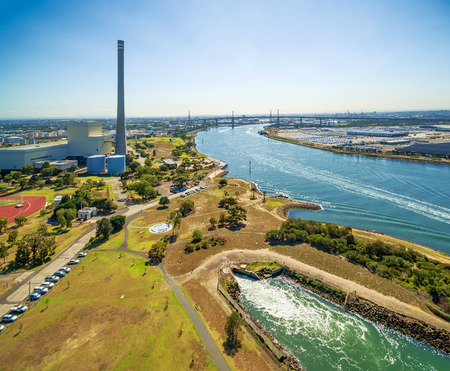 Aerial view of Newport Power Station, West Gate Bridge, and Yarra River at high noon. Melbourne, Victoria, Australia