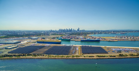 Aerial Panorama of Port Melbourne with docked Carr Carriers, Yarra River, and Melbourne CBD skyline on the horizon. Melbourne, Victoria, Australia Éditoriale