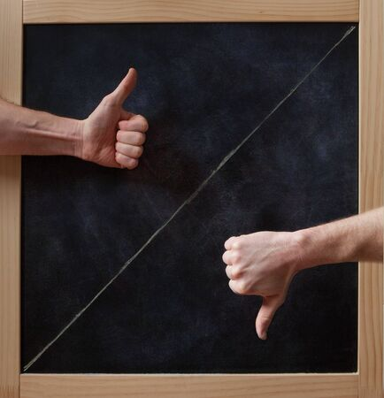 diagonal: Thumbs up and down concept on blackboard