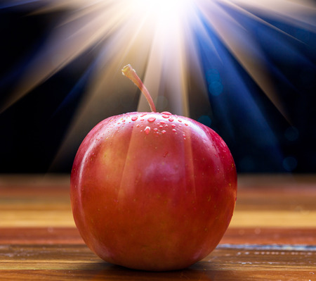 Red Fuji apple with water drops and light flare on wooden table and black background Stock Photo