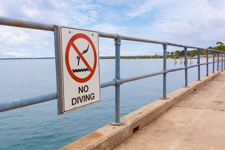No Diving sign on a pier railing with ocean water in the background