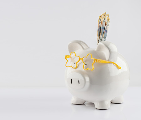 Piggy bank with yellow glasses and three 50 dollar bills isolated on white