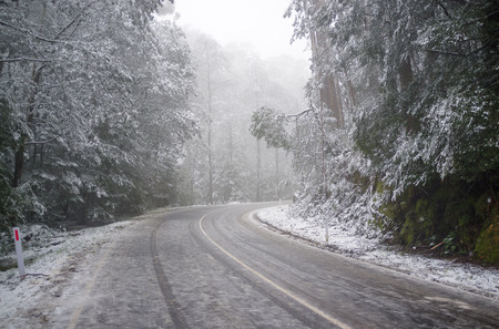 Slippery and icy winding mountain road under heavy snowfall, Victoria, Australia