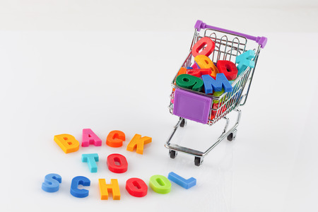 Toy shopping cart filled with letters and numbers - back to school concept isolated on white