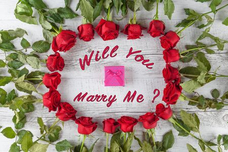 Will you marry me? text with small gift box in a circle of red roses on white wooden table. Top view.