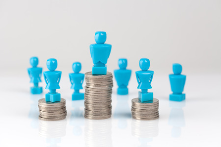 Male and female figurines standing on top of coin piles with other figurines in the background. Wage gap and corporate structure concept.
