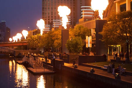 Melbourne CBD - APR 16 2016: Crown Casino fire show - powerful bright flames emitting from industrial structures with people watching. Editorial