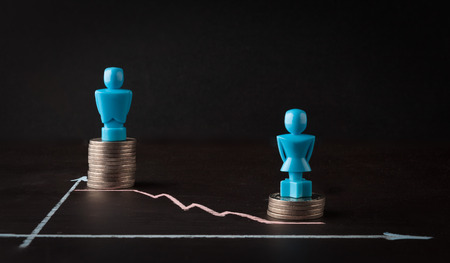 Wage gap and gender equality concept depicted with male and female figurins standing on top of coin piles and line graph Banco de Imagens - 79405109