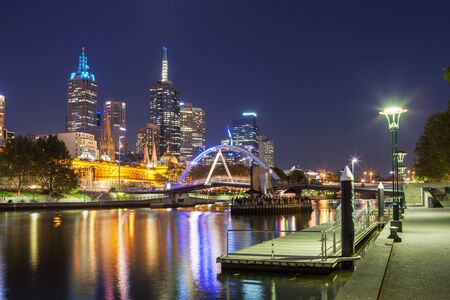 southbank: Melbourne CBD - APR 17 2016: Cityscape at night with Southbank footbridge over yarra river and Flinders street station.