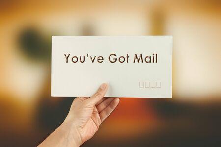 Female hand delivering a postage envelope on blurred colorful background. Image has vintage filter applied Foto de archivo