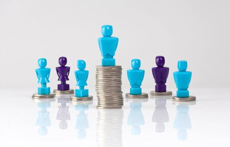 Wage gap and unequal money distribution concept shown with male and female figurines standing on coin piles 写真素材