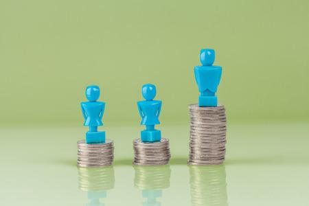 salarios: Figuras masculinas y femeninas de pie en la parte superior de las columnas de monedas. Concepto de concepto de hueco salarial.