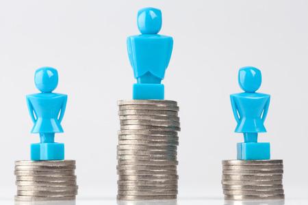 Een mannelijke en twee vrouwelijke beeldjes staan ??op stapels munten. Held kijk. Inkomensongelijkheid concept. Stockfoto
