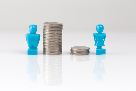 Income inequality concept shown with male and female figurines and piles of coins