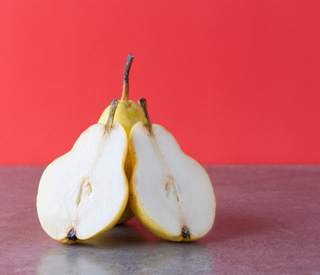 Whole and halved yellow Corella pears on red background with copy space