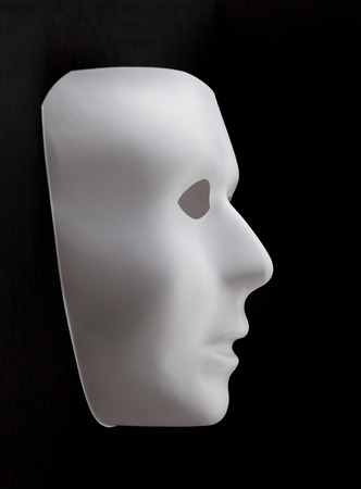 White mask emerging from black background.