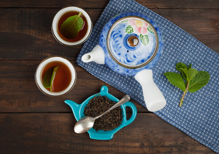 Whole leaf tea with teapot and two cups on towel and wooden background. Top view. Stock Photo
