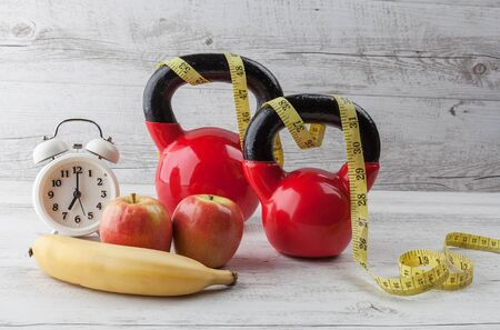 Two red kettlebells with measuring tape, apples, banana, and vintage clock on rustic white wooden table. Healthy diet and fitness concept. Banco de Imagens - 79519868