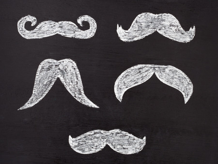 Set of white moustaches hand drawn with chalk on blackboard. Movember mens health awareness concept.