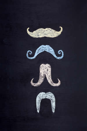 Set of colorful moustaches hand drawn with chalk on blackboard. Movember mens health awareness concept.
