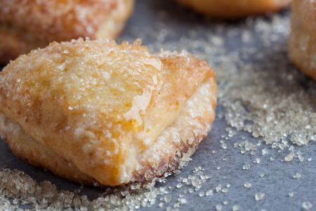 Sweet cottage cheese cookie covered in sugar crystals and honey extreme closeup