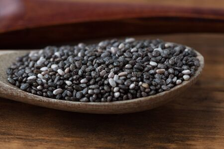 Black Chia seeds in wooden spoon extreme closeup