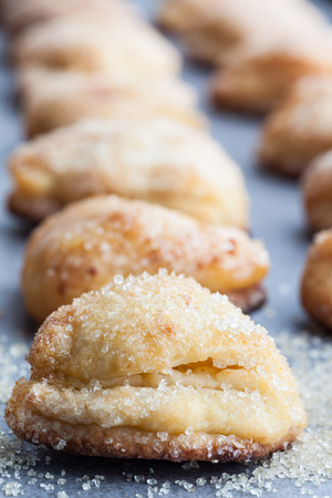 Vertical row of cottage cheese cookies sprinkled with sugar. Shallow depth of field.