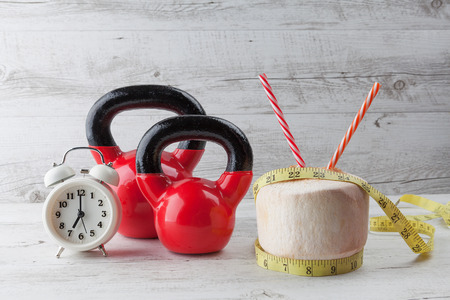 Two red kettlebells with measuring tape, drinking coconut, straws, and vintage clock on rustic white wooden table. Healthy diet and fitness concept.