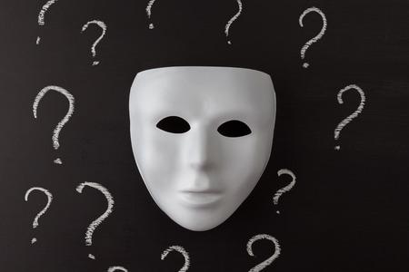 Weiße Maske auf schwarzem Hintergrund mit Hand gezeichneten KreideFragezeichen. Wer bin ich ? Identitätskonzept. Horizontales Bild. Standard-Bild