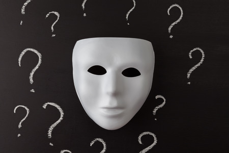 White mask on black background with hand drawn chalk question marks. Who am I ? Identity concept. Horizontal image.