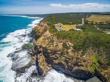 Aerial view of Cape Schanck Lighthose and waves crushing over rugged coastline. Mornington Peninsula, Victoria, Australia