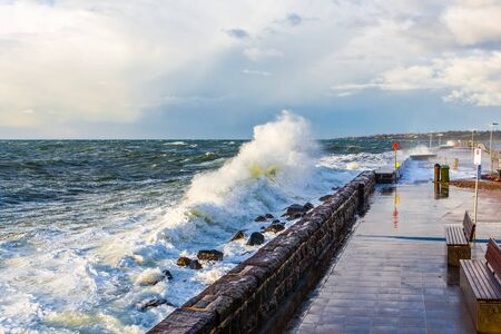 Big wave coming up to pier and breakwater. Mornington Peninsula, Victoria, Australia